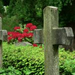 Steinkreuze vor einer Hecke