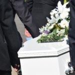 Sargträger tragen einen weißen Sarg bei Bestattungszeremonie von Bestattungen Männer